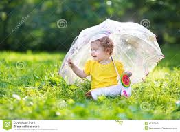 cute baby in garden under an umbrella stock photo