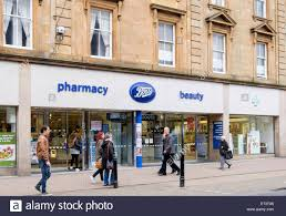 shop boots chemist boots pharmacy store shop front with shoppers passing outside on