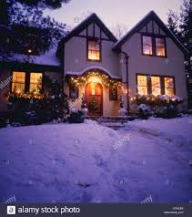 english tudor style home with snow and christmas decorations stock