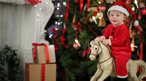 Christmas Tree Costume For Kids - part of body of little kid in santa costume on rocking horse near