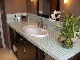 acryclic white sink and small green porcelain tile countertop