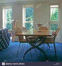 pale wood table and wicker metal chairs in modern dining room with