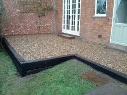 railway sleeper walls and gravel patio built in rear garden