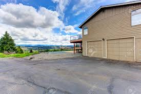 house with two car garage and driveway view of backyard tennis