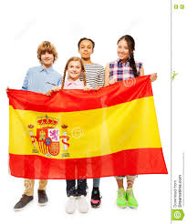 four multiethnic teenage kids holding spanish flag stock photo