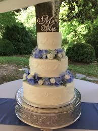 three tier buttercream wedding cake decorated with silk flowers