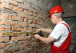 house builder in uniform with a tape line against the brick wall