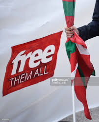 Outside Flag Topshot A Woman Holds A Basque Flag As People Gather Outside The