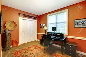 home office room with bright orange walls and carpet floor