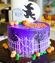 a spooky graveyard and witch cake for a halloween birthday cake