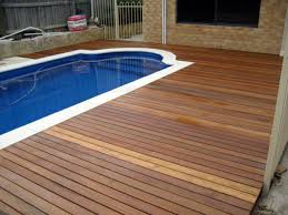 white pool with brown wooden deck plus grey wooden fence and brown