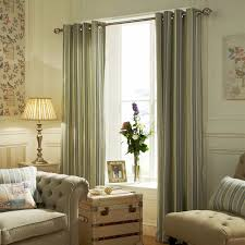 living room with vertical pattern eyelet curtains and pale wall
