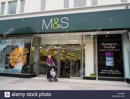 marks and spencer bureau a senior citizen with baby in pushchair leaves a marks and
