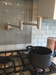 adorable pot filler faucet with black pan and cooktop also grey