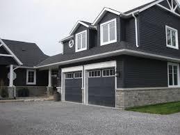 dark blue grey vinyl siding on a house with stone veneer around