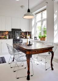 white kitchen island with silver countertop black tile backsplash