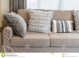 sturdy brown sofa with grey patterned pillows stock photo image