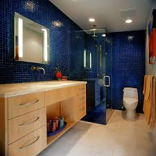 narrow bathroom with walk in shower and blue glass wall tiles also