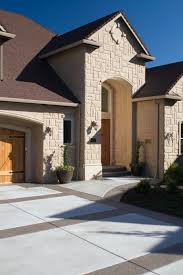 a gorgeous stone home exterior with a wood garage door and stained