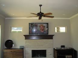 interior mounting tv above fireplace with ceiling fan also white