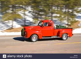 ford truck red santa driving a vintage red ford pick up truck down a paved rural