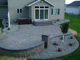 earth tone paver patio with sitting wall and rock fill edging