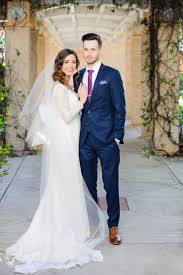 grooms wedding attire couples photos in lace gown with groom in blue suit