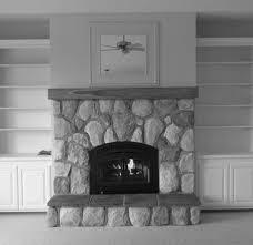 natural gray stone wall panel above gray iron fireplace mantel