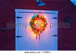 lighted christmas wreath lighted christmas wreath on the door of a barn at a rural