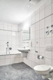 white tiled bathroom with lavatory tub toilet and mirror stock