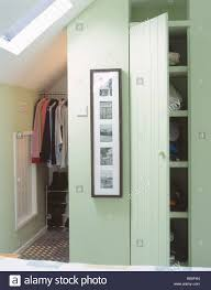clothes on hanging rail and cupboard door open on storage shelves