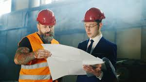 architect and builder in a helmet with a beard together studying