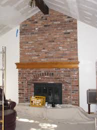 brick fireplace with brown wooden mantel shelf and black fire box