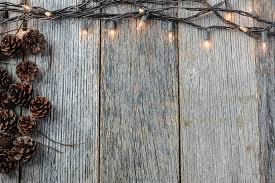 rustic christmas christmas lights and pinecones on rustic wood background brandon