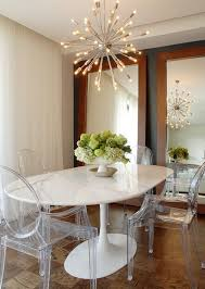 white lacquered oval kitchen table and clear acrylic dining chairs