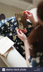 young woman in pretty dress looking at a photograph of a couple on