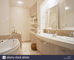 mirrors above double basins built into vanity unit in modern