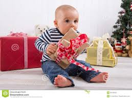 first christmas baby unwrapping a present stock photography