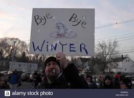 man holds up bye bye winter sign on groundhog day in milltown nj