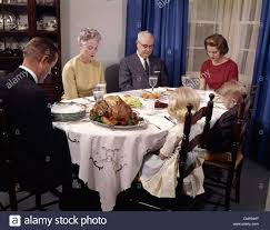 thanksgiving dinner blessing prayer 1960s three generation family saying grace at thanksgiving dinner
