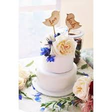 rustic white wedding cake with blue white flowers and wood bird