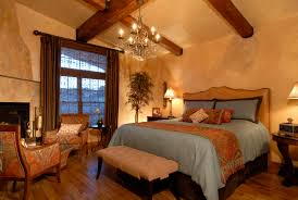warm and charming tuscan style master bedroom with huge bed and a