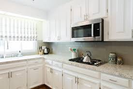 white kitchen cabinets with taupe backsplash an update kitchen with white cabinets and taupe ceramic