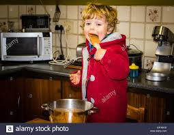 little boy licking a chocolate cake batter spoon in country