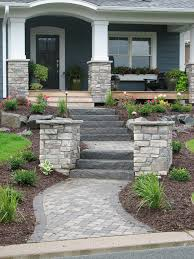paver walkway natural stone steps and flanking pillars create a