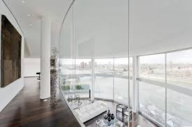a glass staircase leads up to a sprawling glass walled mezzanine