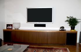 white wooden floating media console with doors and racks on white