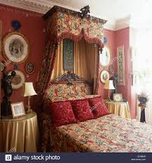 rich tapestry drapes on half tester bed with red velvet cushions