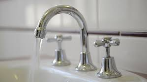 Bathroom Water Faucet by Woman Turning Off Water Bathtub Faucet In The Bathroom Stock