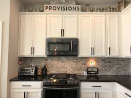 white cabinets with black countertops and appliances kitchen up of the back splash purhcased from